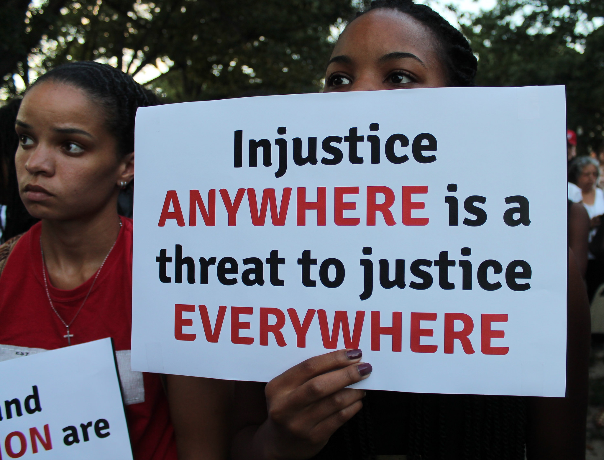 A protester holds a sign at a moment of silence for Michael Brown at Meridian Hill Park in D.C. in August.