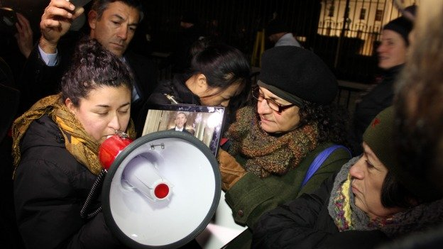 Immigration activists listen to President Barack Obama's speech on an iPad outside the White House as a translator provided details on the immigration plan being unveiled on Nov. 20, 2014.