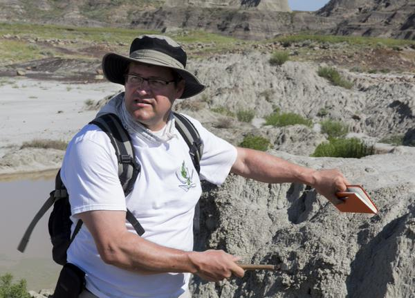 Smithsonian's National Museum of Natural History director Kirk Johnson examines what was once a Late Cretaceous landscape, in North Dakota's Hell Creek Formation in July 2013.