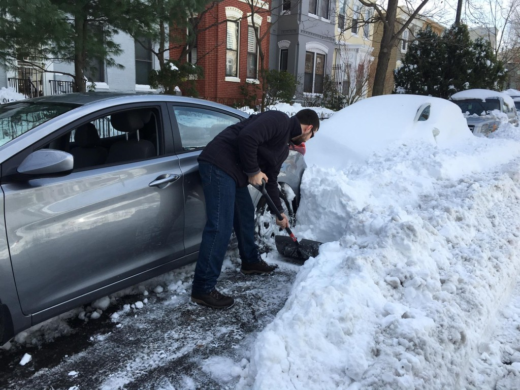 A D.C. resident shovels his car out of the snow.