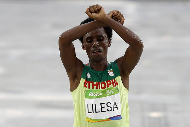 Ethiopian runner Feyisa Lilesa crosses his arms in protest of the persecution of the Oromo people as he crosses the Olympic marathon line in Rio de Janeiro.