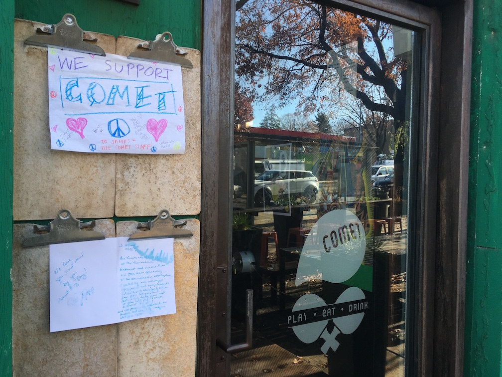 Signs supporting Comet Pizza outside the restaurant's door.