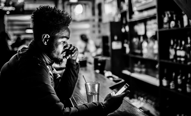 A man checks his phone at a bar in Northeast D.C.