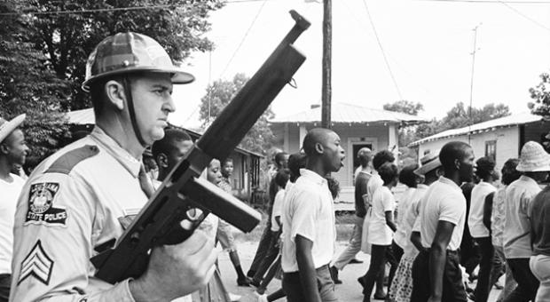 A heavily armed white trooper menacing a protest march through Bogalusa, Louisiana, in 1965.